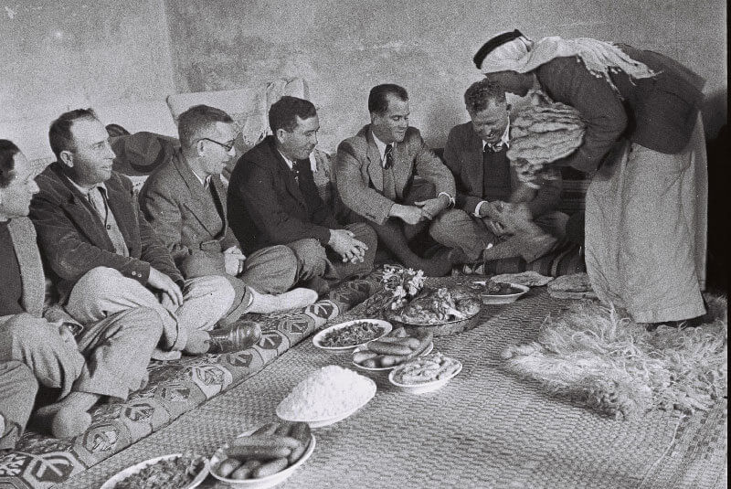 JEWISHSETTLERS FROM ZICHRON YA'ACOV BEING SERVED A MEAL AT THE HOME OF JABRI AMIN EL HAJ AT THE NEIGHBORING ARAB VILLAGE OF SUBRIN 1949.
