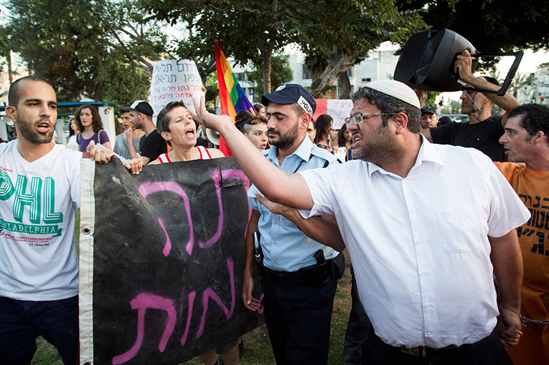Itam Ben Gvir argue with LGTBQ activists as they protest against homophobia and racism in front of right-wing settlers and a small group of south Tel Aviv residents marching against African asylum seekers, in Levnisky park, South Tel Aviv, August 19, 2015.