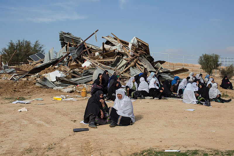 "Bedouin women sit in front of the ruins of their houses in the unrecognized Arab/Palestinian Bedouin village of Umm Al-Hiran, in the Negev desert, January 18, 2017. A resident and an Israeli policeman were killed during the operation. Israeli authorities said the policeman was killed in a car-ramming attack while residences and activists claimed the driver was first shot dead by police with ""no reason"" before losing control on his car and driving towards policemen."